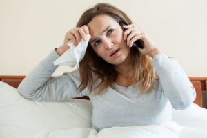 woman sick in bed on phone