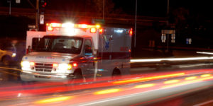 ambulance driving very fast on city street with blurry lights passing